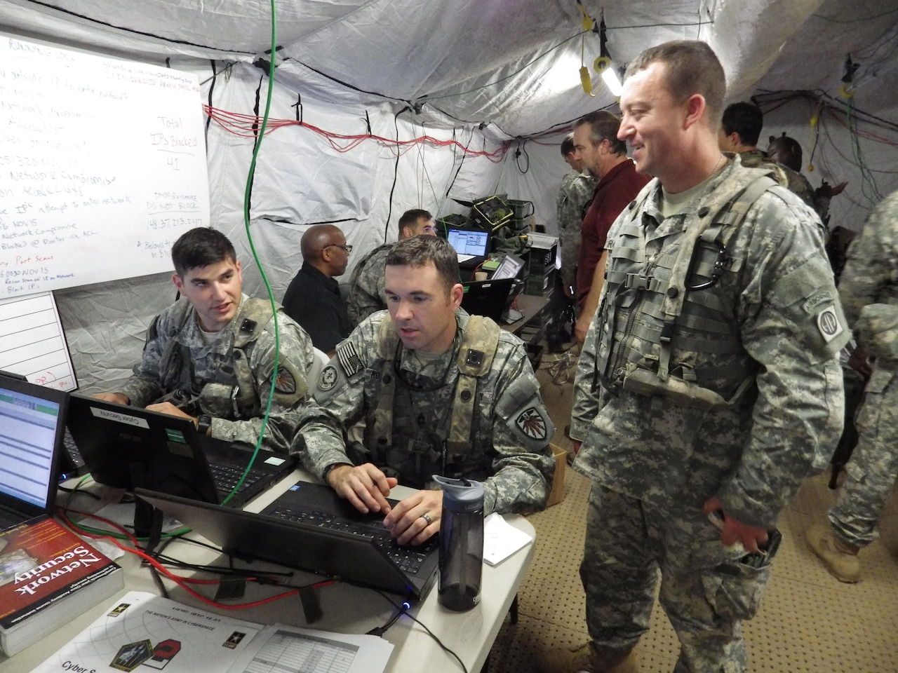 Army Sgts. 1st Class Richard Miller, left, and Brian Rowcotsky, center, of the U.S. Army Cyber Protection Brigade discuss the response to a simulated cyberattack on the 1st Brigade Combat Team, 82nd Airborne Division, with Army Staff Sgt. Frederick Roquemore, a cyber network defender with the brigade, at the Joint Readiness Training Center at Fort Polk, La., Nov. 6, 2015. The Defense Department's innovation outpost in Silicon Valley is hosting an information meeting with Army and Defense Advanced Research Projects Agency officials March 31, 2016, to highlight potential contracting opportunities. Army photo by Bill Roche