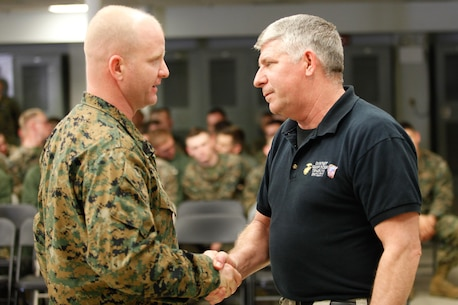 Harrisonburg, Va.-native 1st Sgt. Matthew A. Moore, left, company first sergeant of headquarters and service company, Chemical Biological Incident Response Force (CBIRF), U.S. Marine Corps Forces Command (MARFORCOM), shakes hands with Patrick Higgins, Downey Responder Training Facility lead instructor with CBIRF prior to a CBIRF Basic Operations Course graduation ceremony at Naval Support Facility Indian Head, Md., Mar. 11, 2016. The course is a three-week program that provides approximately 145 hours of classroom, practical applications and individual and team testing in chemical, biological, radiological, nuclear, and high-yield explosive disciplines that meet federal requirements. After graduating the course, each Marine and sailor will be qualified to enter a contaminated area, search the area, provide emergency first aid and provide assistance to nonambulatory patients. Regardless of their jobs, or military occupational specialty, every Marine and sailor with CBIRF is required to complete the course, making the unit uniquely qualified to respond with minimal warning to a chemical, biological, radiological, nuclear or high-yield explosive (CBRNE) threat. (Official USMC Photos by Sgt. Jonathan S. Herrera/Released)
