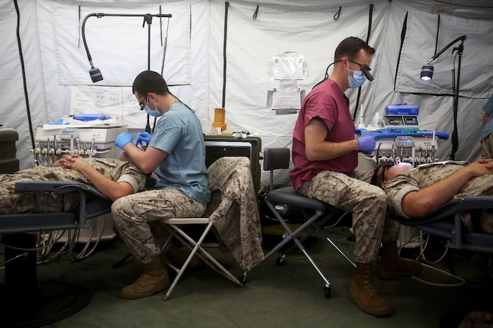 Lieutenants Eric Appelseis, left, and Matt Kanter, right,  treat patients during Authorized Dental Allowance List Exercise aboard Camp Pendleton, Calif., March 13-25, 2016. Appelseis and Kanter are both dental officers with 1st Dental Battalion, 1st Marine Logistics Group. ADALEX, which is being conducted for the first time in 10 years, is intended to increase the unit's expeditionary dental capabilities by operating in a field environment. (U.S. Marine Corps photo by Cpl. Carson Gramley/released)