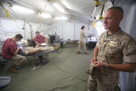 Captain Peter Ruocco observes the patients being treated during Authorized Dental Allowance List Exercise aboard Camp Pendleton, Calif., March 13-25, 2016. Ruocco is the commanding officer of 1st Dental Battalion, 1st Marine Logistics Group. ADALEX, which is being conducted for the first time in 10 years, is intended to increase the unit's expeditionary dental capabilities by operating in a field environment.  (U.S. Marine Corps photo by Cpl. Carson Gramley/released)
