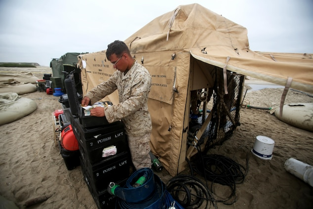 Corporal Tyler Schneider, a water support technician with Utilities Platoon, Headquarters and Support Company, 7th Engineer Support Battalion, 1st Marine Logistics Group, retrieves the required supplies to maintain a tactical water purification system during a utilities exercise at Red Beach aboard Camp Pendleton, Calif., March 21, 2016. Utilities Platoon conducted an eight-day field exercise which focused on their ability to provide clean water and stable power to a unit located in an environment without standard utility resources. (U.S. Marine Corps photo by Cpl. Carson Gramley/released)