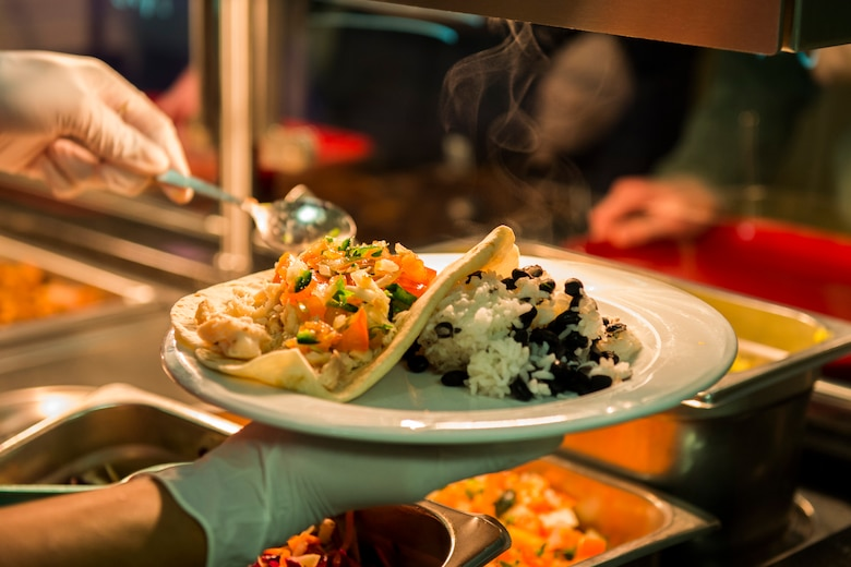 A member of the 52nd Force Support Squadron puts together a plate of food during the Messlords luncheon at the Mosel Dining Facility at Spangdahlem Air Base, Germany, March 30, 2016. The culinary creations of the Messlords included a green chili with pork, marinated fish tacos, rice, beans, homemade guacamole and pico de gallo. (U.S. Air Force photo by Senior Airman Luke Kitterman/Released)