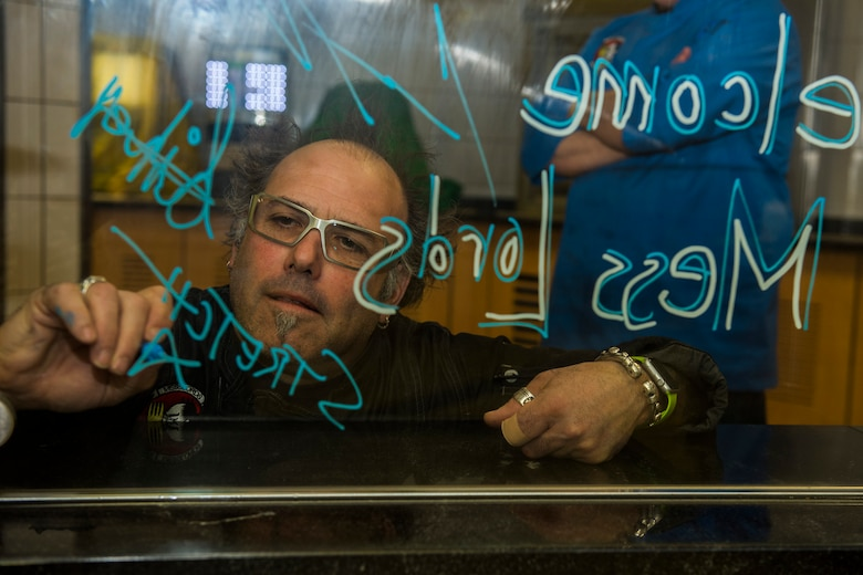 Stretch, a Messlords member, signs his name on a piece of glass at the Mosel Dining Facility at Spangdahlem Air Base, Germany, March 30, 2016. Stretch, owner of 'Grinders' restaurants in Kansas City, Mo., is one of four original Messlords and has been providing service members meals  through the tour for seven consecutive years. (U.S. Air Force photo by Senior Airman Luke Kitterman/Released)