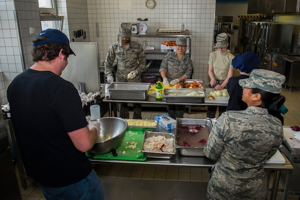 Members of the 52nd Force Support Squadron prepare food in the kitchen of the Mosel Dining Facility at Spangdahlem Air Base, Germany, March 29, 2016. More than 25 members of the 52nd FSS coordinated the Messlords luncheon, an event involving three celebrity chefs providing lunch for the Spangdahlem community. (U.S. Air Force photo by Senior Airman Luke Kitterman/Released)