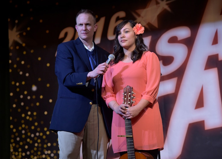 Matthew Jobe, the community service flight chief with the 35th Force Support Squadron, holds a microphone up to Nadine Leon Guerrero, a Misawa Stars contestant, after her performance at Misawa Air Base, Japan, March 25, 2016. Misawa Stars is an opportunity to showcase the base's top singers. This year's competitors were comprised of active-duty members, dependents, and local Japanese nationals.  (U.S. Air Force photo by Senior Airman Deana Heitzman)
