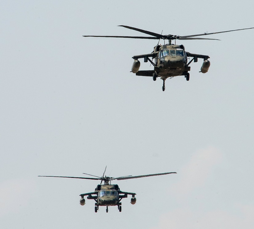 Two U.S. Army UH-60 Black Hawks depart Soto Cano Air Base in support of firefighting efforts on the North coast of Honduras, Mar. 31, 2016, after Juan Orlando Hernandez, President of Honduras, sent a request for support to the U.S. Ambassador in Honduras. The helicopters, assigned to the 1-228th Aviation Regiment, maintain Bambi Bucket and hoist capabilities, allowing them to support Honduran fire response forces fighting fires like those affecting the Jeanette Kawas National Park in northern Honduras. (U.S. Air Force photo by Capt. Christopher Mesnard/Released)