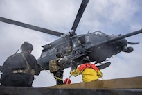 An airman communicates with a crew chief in a HH-60G Pave Hawk helicopter participating in a simulated casualty evacuation training exercise off the coast of Homer, Alaska, April 27, 2016. Air National Guard photo by Staff Sgt. Edward Eagerton