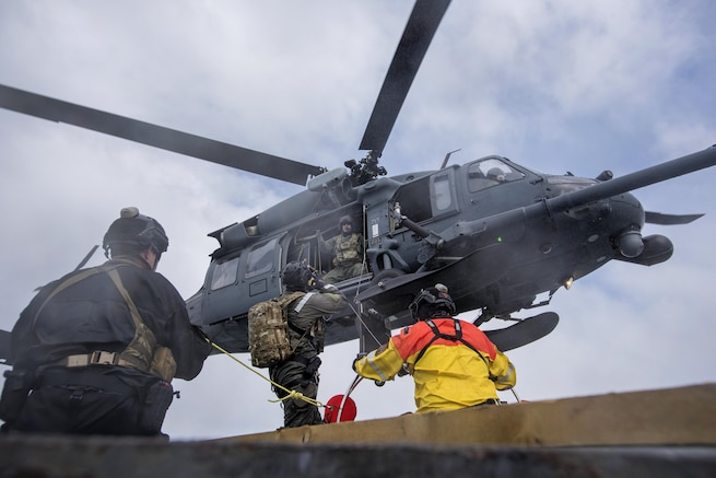 An airman communicates with a crew chief in an HH-60G Pave Hawk helicopter participating in a simulated casualty evacuation training exercise off the coast of Homer, Alaska, April 27, 2016. Air National Guard photo by Staff Sgt. Edward Eagerton