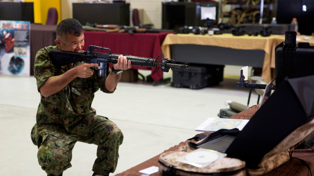 """A Japan Ground Self-Defense Force member visiting the annual Training Expo at Camp Hansen, Okinawa, Japan tests out the Instrumental Tactical Evaluation Simulated System on Friday, April 29, 2016. This recently updated system works almost like the popular game, """"laser tag,"""" where a laptop traces the marksmanship of the shooter. This training can be recorded and handed back to the unit on a CD to evaluate performance."""