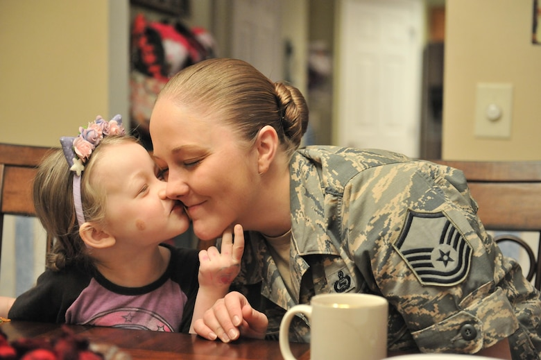 Gracie kisses her mother Stephanie, a master sergeant with the 707th Intelligence Surveillance and Reconnaissance Group, after eating breakfast April 13, 2016 in Laurel, Md. Stephanie has been enrolled in the Exceptional Family Member Program because of Gracie's rare disorder, Systemic Autoinflammatory Disorder. The family has been accepted into a National Institutes of Health clinical trial which helps with medication and treatments. (U.S. Air Force photo/ Staff Sgt. Alexandre Montes)