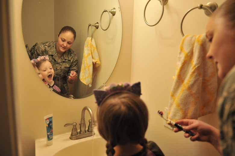 Stephanie, a Master Sgt. with the 707th Intelligence Surveillance and Reconnaissance Group, helps Gracie brush her teeth before going to school April 13, 2016 in Laurel, Md. Stephanie has been enrolled in the Exceptional Family Member Program because of Gracie's rare disorder, Systemic Autoinflammatory Disorder. The family has been accepted into a National Institutes of Health clinical trial which helps with medication and treatments. (U.S. Air Force photo/ Staff Sgt. Alexandre Montes)
