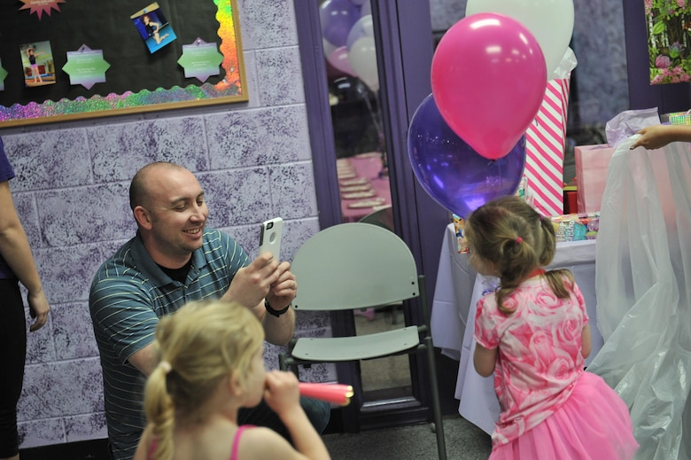 John, a technical sergeant with the 34th Intelligence Squadron, takes a photo of his daughter Gracie during her birthday party April 23, 2016 in Annapolis, Md. John has been enrolled in the Exceptional Family Member Program because of Gracie's rare disorder, Systemic Autoinflammatory Disorder. The family has been accepted into a National Institutes of Health clinical trial which helps with medication and treatments aiding in readjustments. (U.S. Air Force photo/ Staff Sgt. Alexandre Montes)