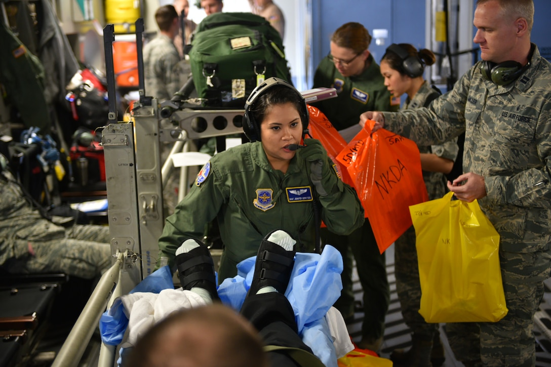 Master Sgt. Jennifer Gerritsen, an aeromedical technician with the 445th Aeromedical Evacuation Squadron, Wright-Patterson Air Force Base, Ohio, helps provide care for wounded warriors while deployed here April 21, 2016. Jennifer and her husband, Kiley, also assigned to the 445th AES, had the opportunity to serve together on this flight as they usually serve on separate crews tasked to rotate moving medical patients from down range to Germany and/or back to the United States. Even though they are on separate crews, their paths often cross as crews help others with preparing the aircraft and loading patients before going off on missions. (U.S. Air Force photo/Tech. Sgt. Frank Oliver)