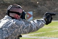 Army Spc. Dylan Lunde fires a 9 mm pistol while wearing a gas mask during the stress shoot event of the Best Warrior Competition at Camp Smith Training Site near Peekskill, N.Y., April 21, 2016. Lunde is a team chief assigned to the New York Army National Guard's 1st Battalion, 258th Field Artillery Regiment. New York National Guard photo by Army Sgt. Michael Davis