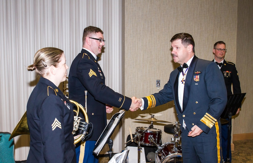 Lt. Gen. Pierre St. Amand, deputy commander for North American Aerospace Defense Command (NORAD), shows his appreciation to the Army's I Corps Band for providing entertainment during the Canadian Mess Dinner April 15 at the American Lake Conference Center, Joint Base Lewis-McChord. (Courtesy photo by Conrad Neumann II)