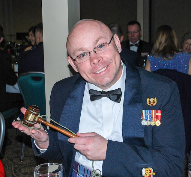 Canadian Warrant Officer Richard Martin takes a moment to show off his newly acquired official mess gavel that Canadian Capt. Stephen Buckley was unable to secure properly as the President of the Mess Committee. The reminder of the night, Buckley had to enforce the mess rules of engagement using a red and blue plastic Fisher Price hammer appropriated from his children's toy box. (U.S. Air National Guard photo by Capt. Kimberly Burke)