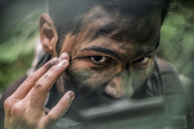 Air Force Capt. Daniel Stancin applies face paint during survival, evasion, resistance and escape training at Yokota Air Base, Japan, April 21, 2016. The training keeps personnel prepared for contingency situations such as evading and escaping capture behind enemy lines. Stancin is a navigator assigned to the 36th Airlift Squadron. Air Force photo by Senior Airman Delano Scott