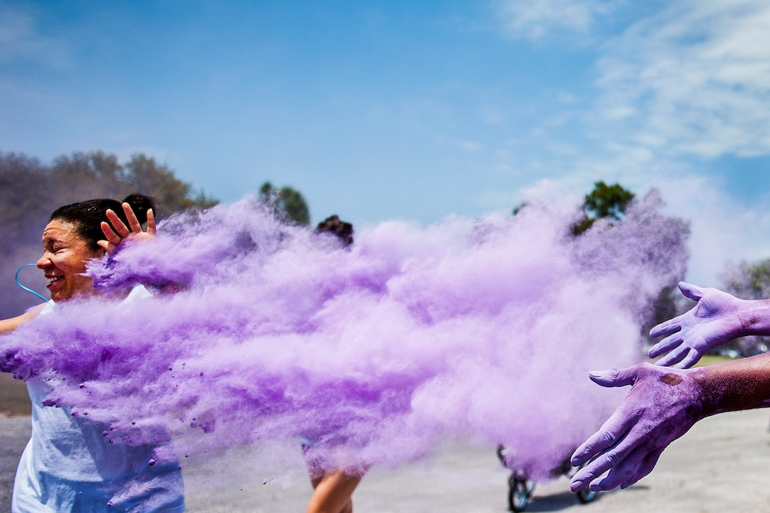 A volunteer showers a runner with a cloud of purple dust at the beginning of the Sexual Assault Prevention and Response Color Run at Eglin Air Force Base, Fla., April 29, 2016. About 300 runners participated in the event. Air Force photo by Samuel King Jr.