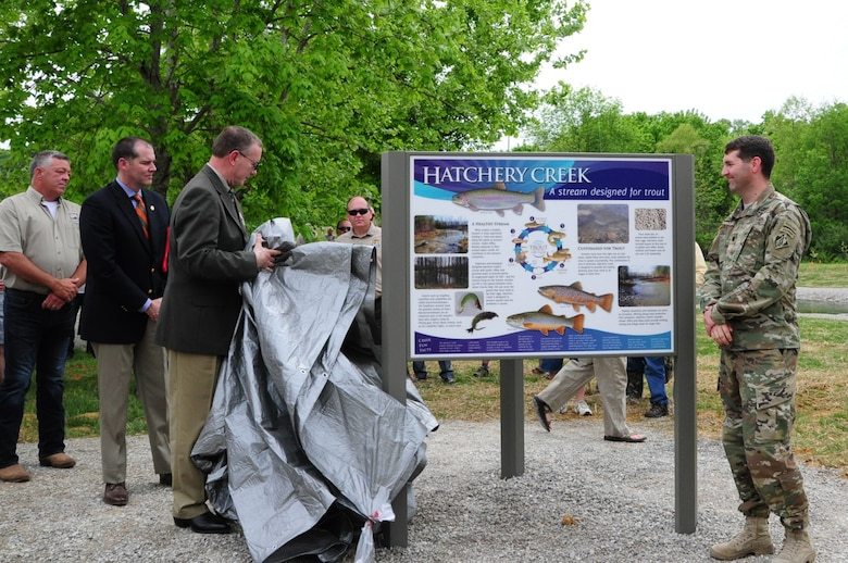 Officials unveil a sign along Hatchery Creek during a dedication ceremony for the stream below Wolf Creek Dam in Jamestown, Ky., April 29, 2016.