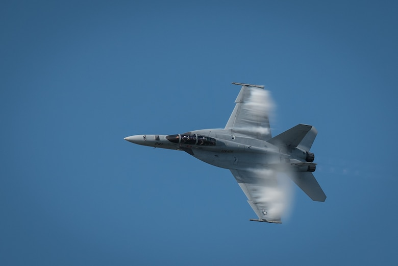 A vapor cloud forms around the fuselage of a U.S. Navy F/A-18 Super Hornet during the fighter jet's demonstration in the Thunder Over Louisville air show over downtown Louisville, Ky., April 23, 2016. Vapor clouds form because air passing over the aircraft at high speeds begins to condense as the temperature drops below the dew point. (U.S. Air National Guard photo by Maj. Dale Greer)