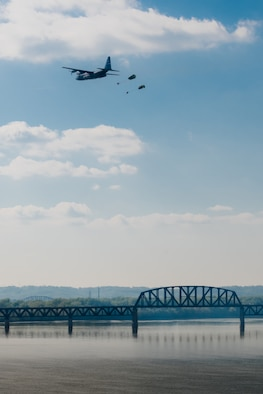 A Kentucky Air National Guard C-130 Hercules transport plane airdrops two bundles of cargo into the Ohio River during the Thunder Over Louisville air show in downtown Louisville, Ky., April 23, 2016. The unit will perform a similar demonstration during the 2017 air show, scheduled for April 22. (U.S. Air National Guard photo by Maj. Dale Greer).