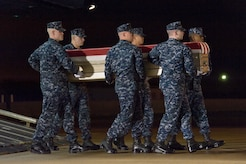 A U.S. Navy carry team transfers the remains of Navy civilian Michael M. Baptiste, of Brooklyn, N.Y., during a dignified transfer May 1, 2016, at New Castle Air National Guard Base, New Castle, Del. Mr. Baptiste was assigned to Forward Deployed Regional Maintenance Center Detachment Bahrain at Naval Support Activity Bahrain. (U.S. Air Force photo/Roland Balik)