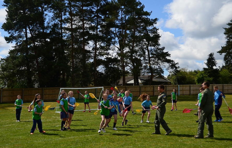 Airmen from the 95th Fighter Squadron at Tyndall Air Force Base, Fla., participate in a game of lacrosse with British students at IES Breckland in Brandon, England, April 26. The Airmen are temporarily deployed to Royal Air Force Lakenheath, England, to conduct air training exercises with U.S. and RAF personnel. During their stay, they visited the school to educate students about the U.S. Air Force, aviation, and fitness, and later participated in a question and answer forum to help the students gain a better understanding about the military lifestyle. (U.S. Air Force photo/Senior Airman Erin Trower)