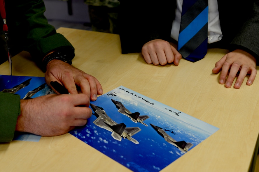 A U.S. Air Force 95th Fighter Squadron F-22 Raptor pilot assigned to Tyndall Air Force Base, Fla., autographs a poster for a British student at IES Breckland in Brandon, England, April 26. The Airmen are temporarily deployed to Royal Air Force Lakenheath, England, to conduct air training exercises with U.S. and RAF personnel. During their stay, they visited the school to educate students about the U.S. Air Force, aviation, and fitness, and later participated in a question and answer forum to help the students gain a better understanding about the military lifestyle. (U.S. Air Force photo/Senior Airman Erin Trower)