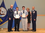 During a retirement ceremony for Air Force Col. Patrick Owens (far right), DLA Troop Support Clothing and Textiles director, Air Force Lt. Gen. William J. Bender, Office of the Secretary of the Air Force chief of information dominance and chief information officer (left) presents Owens' two sons with letters of appreciation. Owens' wife is also pictured. Owens retired after a 30-year career and two years as the C&T director.