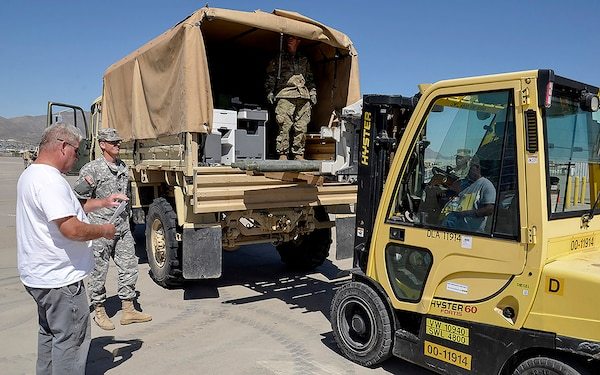 "Ray Menendez (left), a DLA Disposition Services material examiner helps units at Fort Bliss, Texas, turn in excess property as part of ""All Army Divestiture."" Photo by Jeff Landenberger"