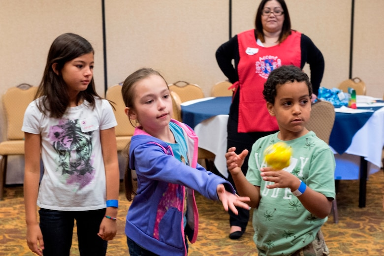 Alexis Badiano, daughter of Maj. Francisco Badiano from the 622nd Civil Engineer Flight at Dobbins Air Reserve Base, Georgia, tosses a ball April 23, 2016, to other children during a game used to teach communication skills at an Air Force Reserve Yellow Ribbon Reintegration Program event in Dallas. During the event children participate in a variety of activities developed to help them cope with the deployment of a military family member. (U.S. Air Force photo/Tech. Sgt. Benjamin Mota)