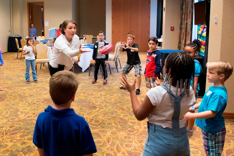 Senior Master Sgt. Jackie Zawada, a program manager with the Air Force Reserve Yellow Ribbon Reintegration Program, plays with children April 23, 2016, during a game used to teach communication skills at a Yellow Ribbon event in Dallas. During the event, children had an opportunity to tell their stories and share their feelings about their parent's recent deployments. (U.S. Air Force photo by Tech. Sgt. Benjamin Mota)