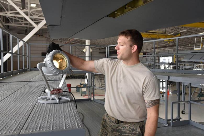 "Staff Sgt. Kevin Cheatham, 403rd Maintenance Squadron Isochronal inspection technician and support equipment manager at Keesler Air Force Base, Mississippi, shows one of the portable lights on the new maintenance platforms, commonly referred to as ""stands,"" April 29, 2016. The squadron recieved the new stands April 14, 2016. The previous stands became outdated, not meeting fall protection limits, and they were not configured all the way around the aircraft. The new stands are placed completely around the aircraft to include the nose and tail sections, provide more working area and access to power and lighting. (U.S. Air Force photo/Maj. Marnee A.C. Losurdo)"