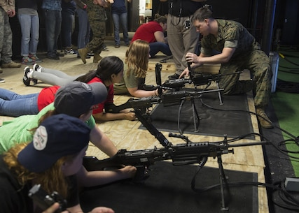 "Spouses and family members of U.S. Marines learn how to properly load the M249 Squad Automatic Weapon during II Marine Headquarters Group's: ""In Their Boots Day"" at Camp Lejeune, N.C., April 29, 2016. The spouses and family members spent a few hours at the Indoor Simulated Marksmanship Trainer getting the opportunity to safely operate the different weapons systems that the Marine Corps uses. (U.S. Marine Corps photo by Cpl. Justin T. Updegraff/ Released)"
