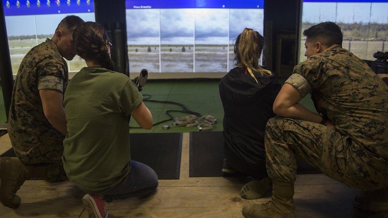 """Marines with II Marine Headquarters Group show their spouses how to operate the M4 Assault Rifle during II MHG's: """"In Their Boots Day"""" at Camp Lejeune, N.C., April 29, 2016. The spouses and family members spent a few hours at the Indoor Simulated Marksmanship Trainer getting the opportunity to safely operate the different weapons systems that the Marine Corps uses. (U.S. Marine Corps photo by Cpl. Justin T. Updegraff/ Released)"""