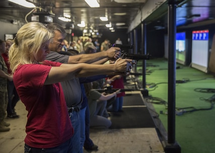 "Family members and spouses shoot the M9 Service Pistol during II Marine Headquarters Group's: ""In Their Boots Day"" aboard Camp Lejeune, N.C., April 29, 2016. The spouses and family members spent a few hours at the Indoor Simulated Marksmanship Trainer getting the opportunity to safely operate the different weapons systems that the Marine Corps uses. (U.S. Marine Corps photo by Cpl. Justin T. Updegraff/ Released)"