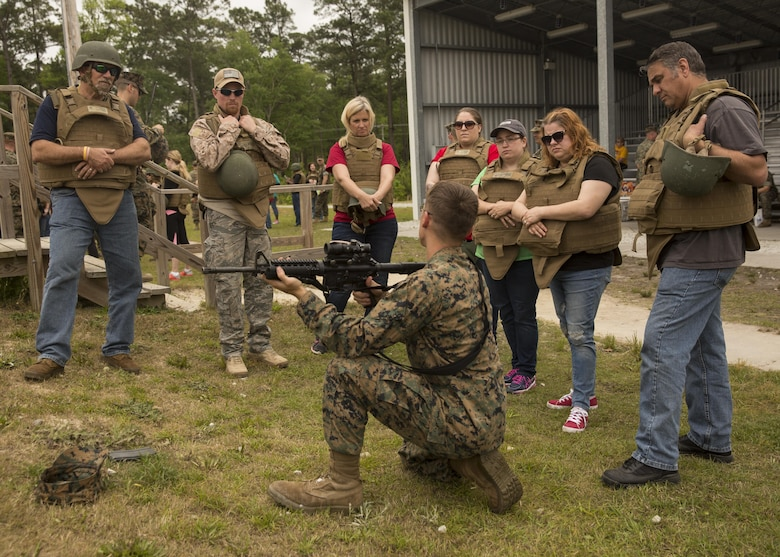 """A U.S. Marine with II Marine Headquarters Group goes over the course of fire with the spouses and family members during II MHG's: """"In Their Boots Day"""" aboard Camp Lejeune, N.C., April 29, 2016. During the course of fire, they shot in the standing, kneeling and prone position and received any needed corrections from the Marine assigned to them. (U.S. Marine Corps photo by Cpl. Justin T. Updegraff/ Released)"""
