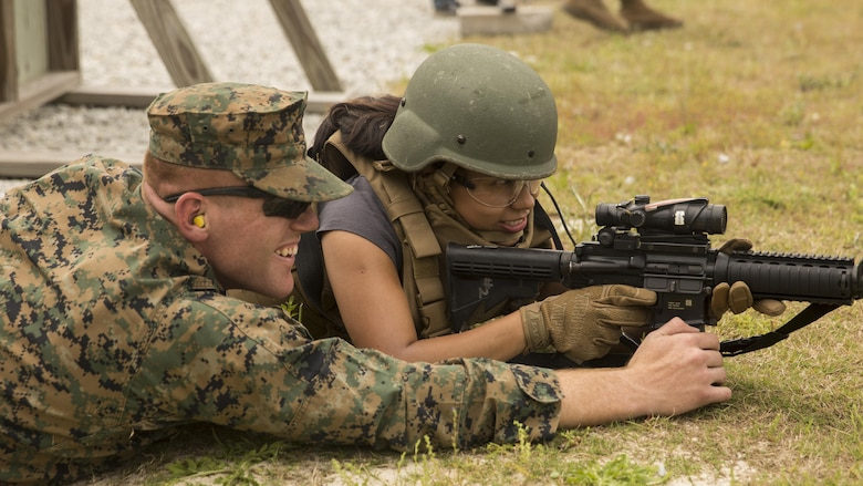 """Yazmine Thomas, a spouse, receives from tips from Lance Cpl. Connor Parks, a water support tech with II Marine Headquarters Group during II MHG's: """"In Their Boots Day"""" aboard Camp Lejeune, N.C., April 29, 2016. During the course of fire, they shot in the standing, kneeling and prone position and received any needed corrections from the Marine assigned to them. (U.S. Marine Corps photo by Cpl. Justin T. Updegraff/ Released)"""