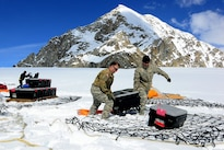 Army Chief Warrant Officers 3 Kirk Donovan, left, and Gene Murray offload equipment and supplies from a CH-47F Chinook helicopter after landing on Kahiltna Glacier, Alaska, April 24, 2016. Donovan and Murray are pilots assigned to Company B, 1st Battalion, 52nd Aviation Regiment. Army photo by John Pennell