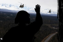 Army Spc. Mark Aderholt waves to two CH-47F Chinook helicopters as they fly back to Talkeetna, Alaska, April 24, 2016, from Kahiltna Glacier in the Alaska Range. Aderholt is a crew chief assigned to Company B, 1st Battalion, 52nd Aviation Regiment. Army photo by John Pennell