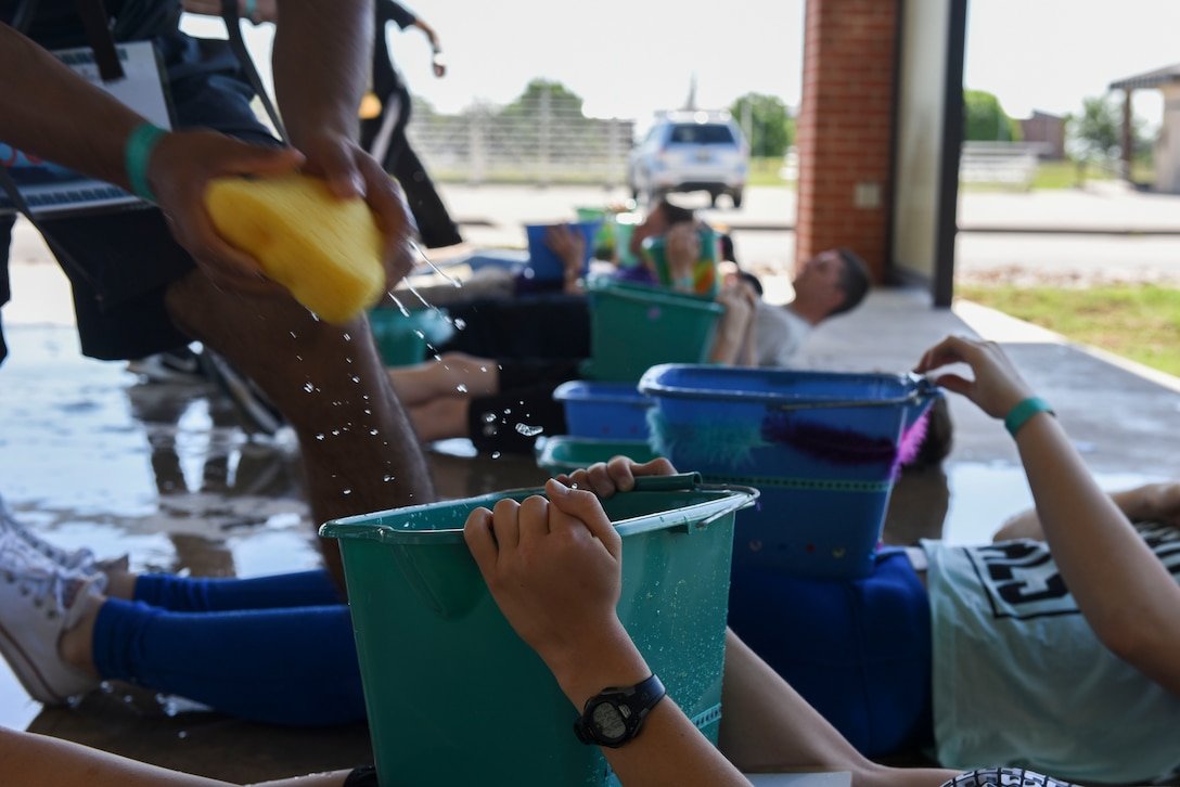 Participants of the sixth annual Sexual Assault Response Coordinator Challenge fill empty buckets with water using sponges at the Parade Field on Goodfellow Air Force Base, Texas, April 30, 2016. The Sexual Assault Prevention and Response staff educated contenders by asking them questions about SAPR. (U.S. Air Force photo by Airman 1st Class Chase Sousa/Released)