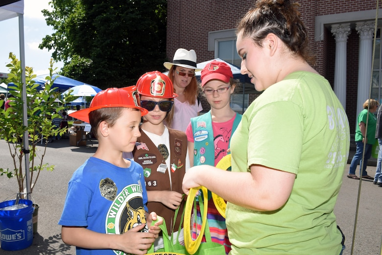 Zoe Roberts, a volunteer with the U.S. Army Corps of Engineers Nashville District, hands out frisbees with water safety messages to kids as part of Earth Day festivities at Town Square in Murfreesboro, Tenn., April 23, 2016. (USACE photo by Leon Roberts)