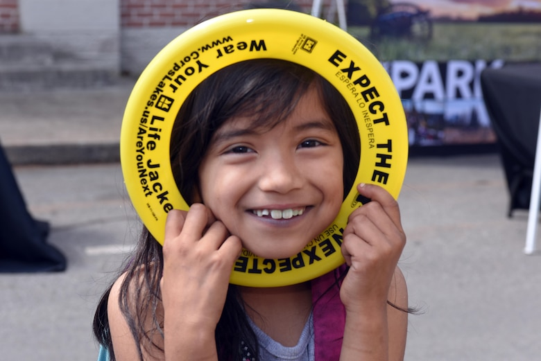 This girl poses with a water safety frisbee she received at the U.S. Army Corps of Engineers Nashville District booth during Earth Day festivities at Town Square in Murfreesboro, Tenn., April 23, 2016.