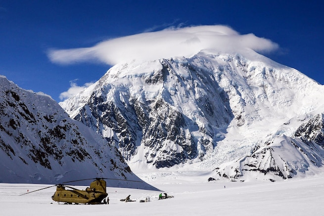 At 17,400 feet, Mount Foraker towers above soldiers as they offload equipment and supplies from a CH-47F Chinook helicopter after landing on Kahiltna Glacier in Denali National Park and Preserve, Alaska, April 24, 2016. Army photo by John Pennell