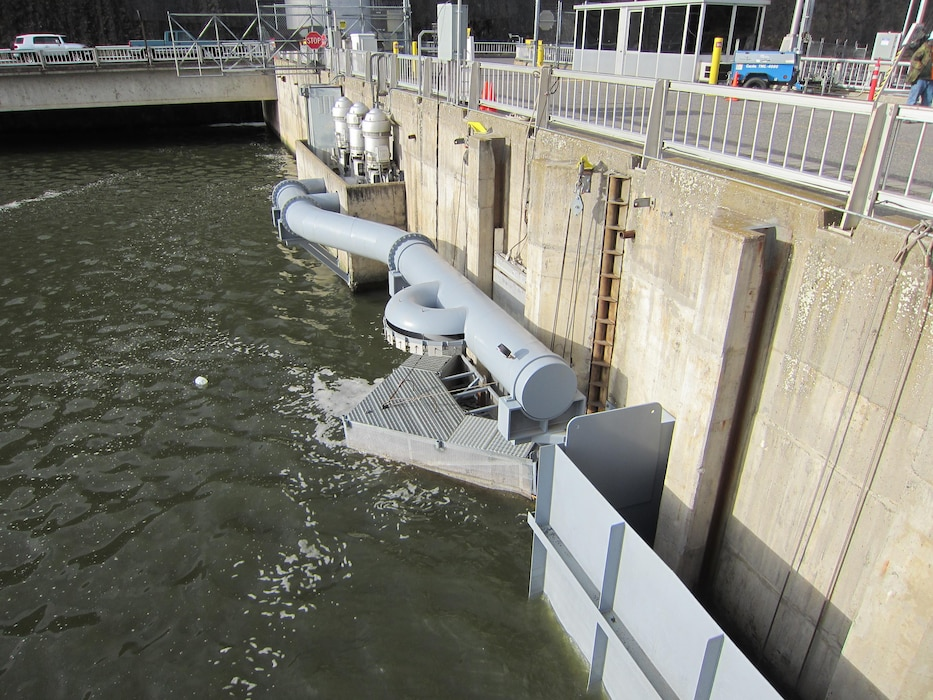 A pump extension intake chimney provides water to the upstream end of the adult fish ladder. The semi-circular pipe sprays water to cool the fish ladder and adjacent forebay area.