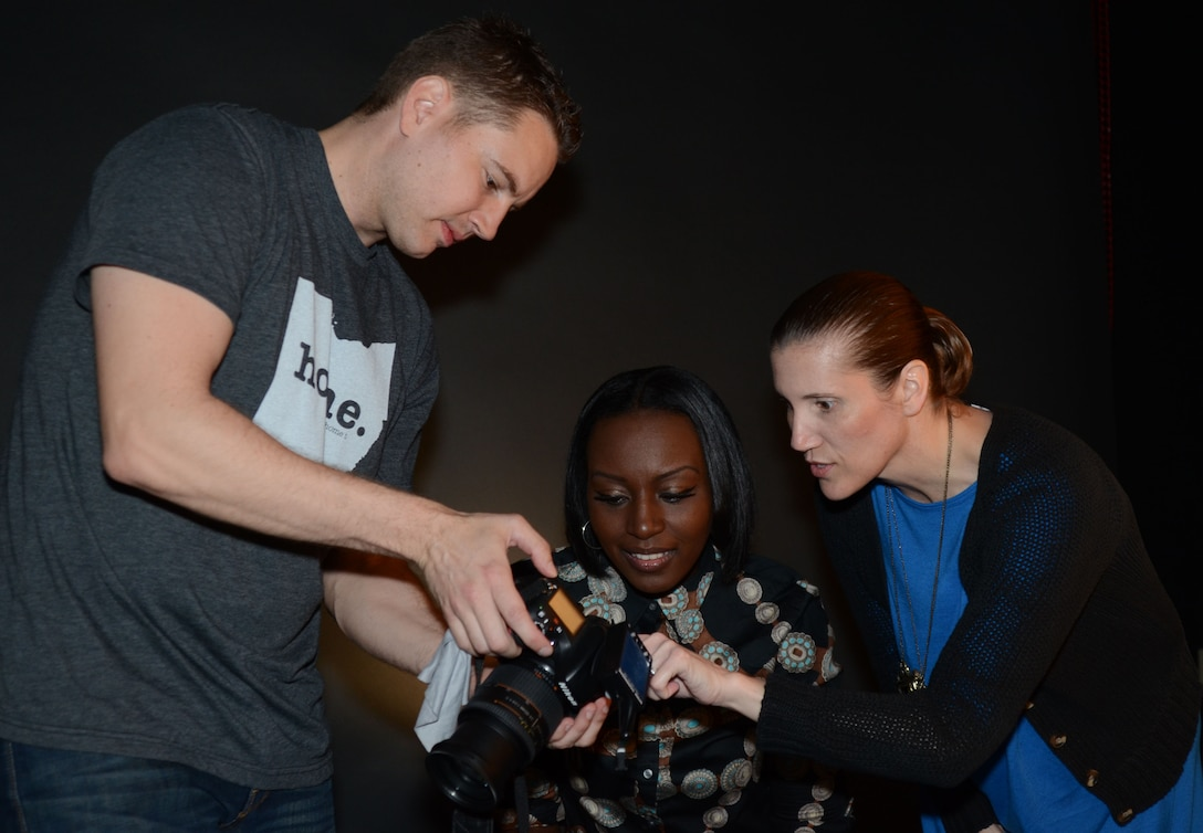 Tracy L. DeMarco, a photojournalism instructor at the Defense Information School on Fort Meade, helps Basic Photojournalist Course-Air Force students Staff Sgt. Tim Mesko, left, and Senior Airman Rana B. Franklin, center, with a studio photography assignment April 22, 2016 at the school. DeMarco, who retired in 2012 after 20 years in the Air Force, joined the DINFOS staff in February to teach photojournalism.