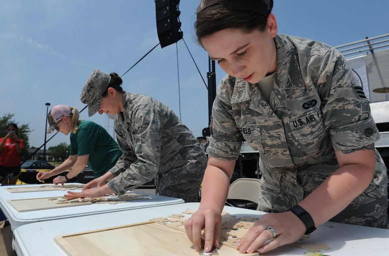 Senior Airman Holly Mansfield, 81st Training Wing Public Affairs photojournalist, assembles a puzzle during a burger burn April 29, 2016, Keesler Air Force Base, Miss. The burger burn was the final event of Wingman Week in support of Comprehensive Airman Fitness. (U.S. Air Force photo by Kemberly Groue)