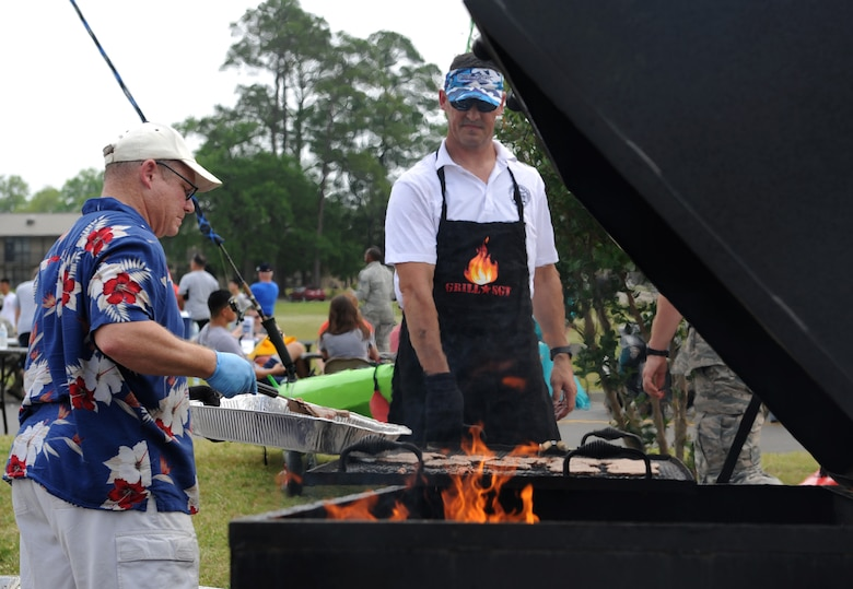 Master Sgt. David Summers, 2nd Air Force software development manager, and Master Sgt. Christopher Walton, 335th Training Squadron first sergeant, grill hamburgers during a burger burn April 29, 2016, Keesler Air Force Base, Miss. The burger burn was the final event of Wingman Week in support of Comprehensive Airman Fitness. (U.S. Air Force photo by Kemberly Groue)