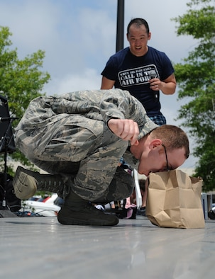 Staff Sgt. Christopher Pineda, 81st Training Support Squadron interactive media developer, competes in the dragon balance competition during a burger burn April 29, 2016, Keesler Air Force Base, Miss. The burger burn was the final event of Wingman Week in support of Comprehensive Airman Fitness. (U.S. Air Force photo by Kemberly Groue)