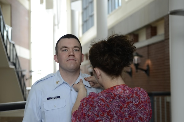 Coast Guard Petty Officer 1st Class Jonathan Lindberg stands at attention as his wife, Hollie Lindberg, pins on his new rank device during an April 1, 2016, ceremony at the Defense Information School on Fort Meade, Md. Lindberg graduated from DINFOS in 2008 and returned as an instructor in 2014.
